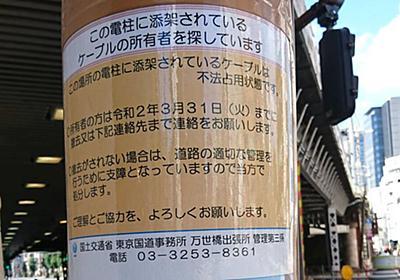 「どうして?」神田駅の電柱のケーブルに正体不明のケーブルがかけられていると貼り紙…一体誰がやったのか? - Togetter